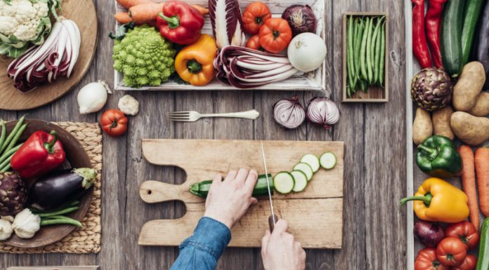 man on vegan diet cutting vegetables on wooden board