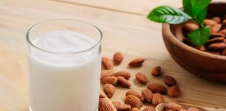 almond milk in a glass next to raw almonds