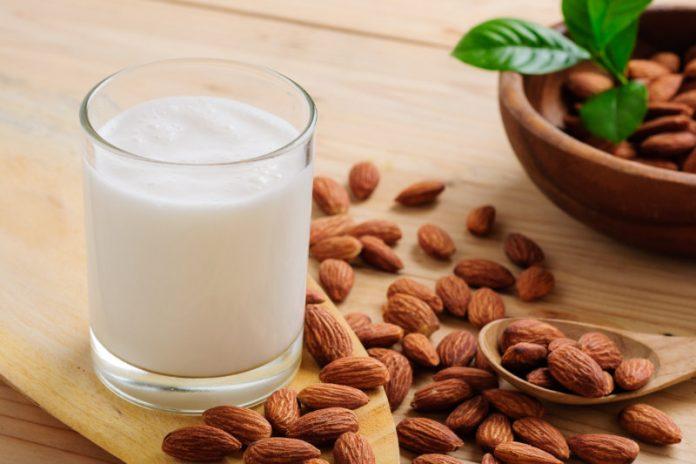almond milk in a glass next to raw almonds