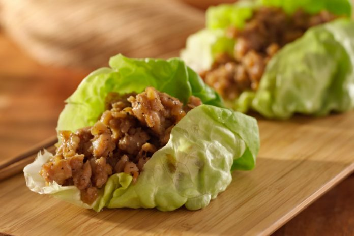 asian chicken filling inside lettuce on a wooden board