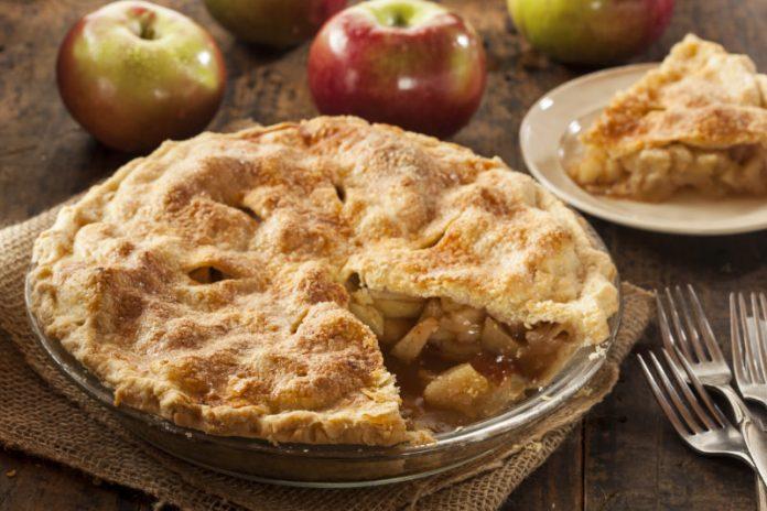 apple pie in a pie dish next to fresh apples