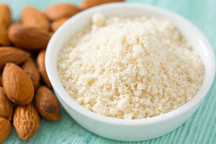 gluten-free baking bowl of almond flour next to raw almonds