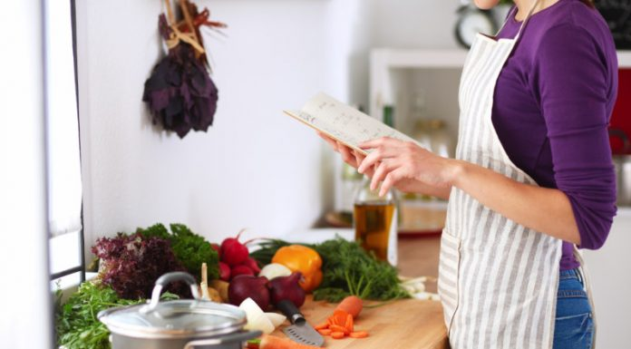 woman using cookbook to make healthy meals