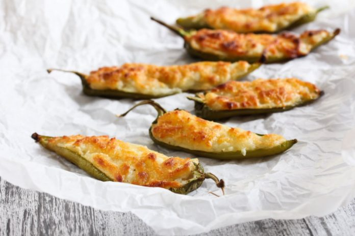 jalapeno poppers on a sheet of parchment paper