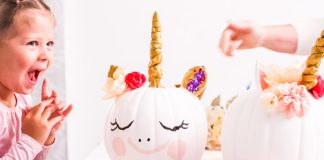 little girl decorating unicorn pumpkin