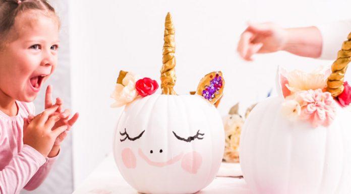 little girl decorating unicorn pumpkin