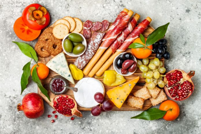 cheese board with fruit, cheese, and charcuterie