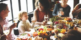 people sitting around a table enjoying thanksgiving dinner